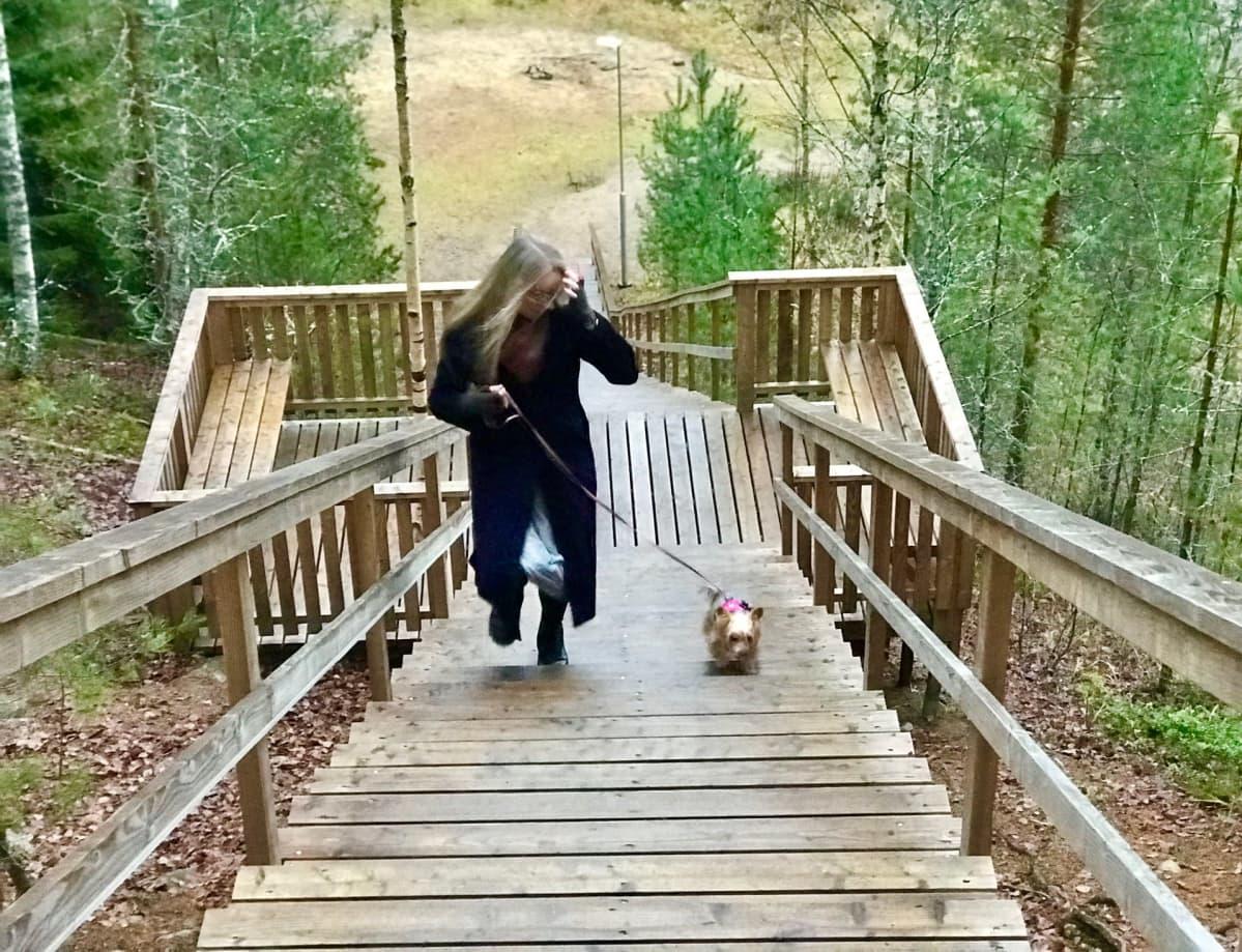 Vaalea, pitkätukkainen nainen lilassa pitkässä takissa juoksee ylös kuntoportaita pienen koiran kanssa