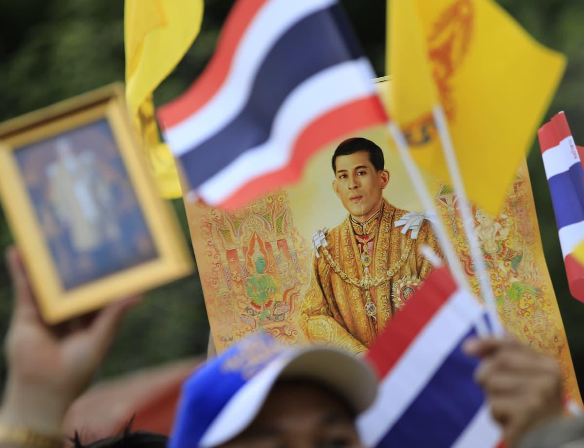 Kuningasta esittävä kuva ja Thaimaan lippuja.