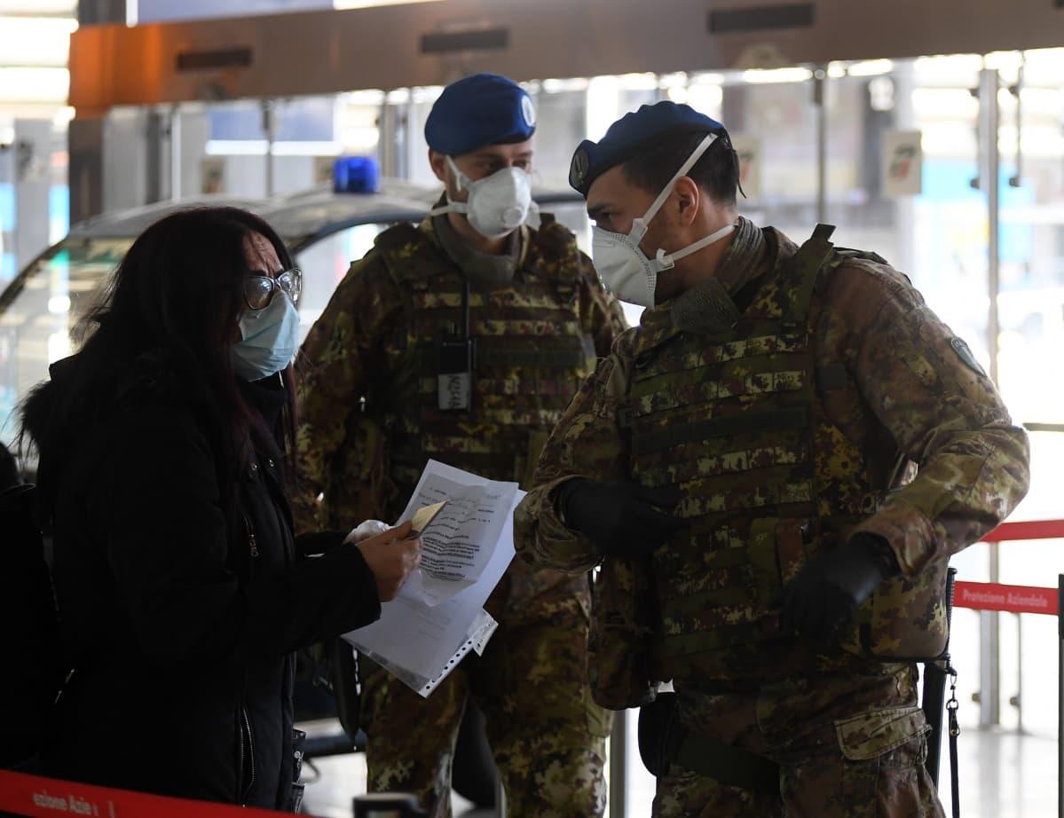 Nainen näyttää papereita kahdelle sotilaalle.