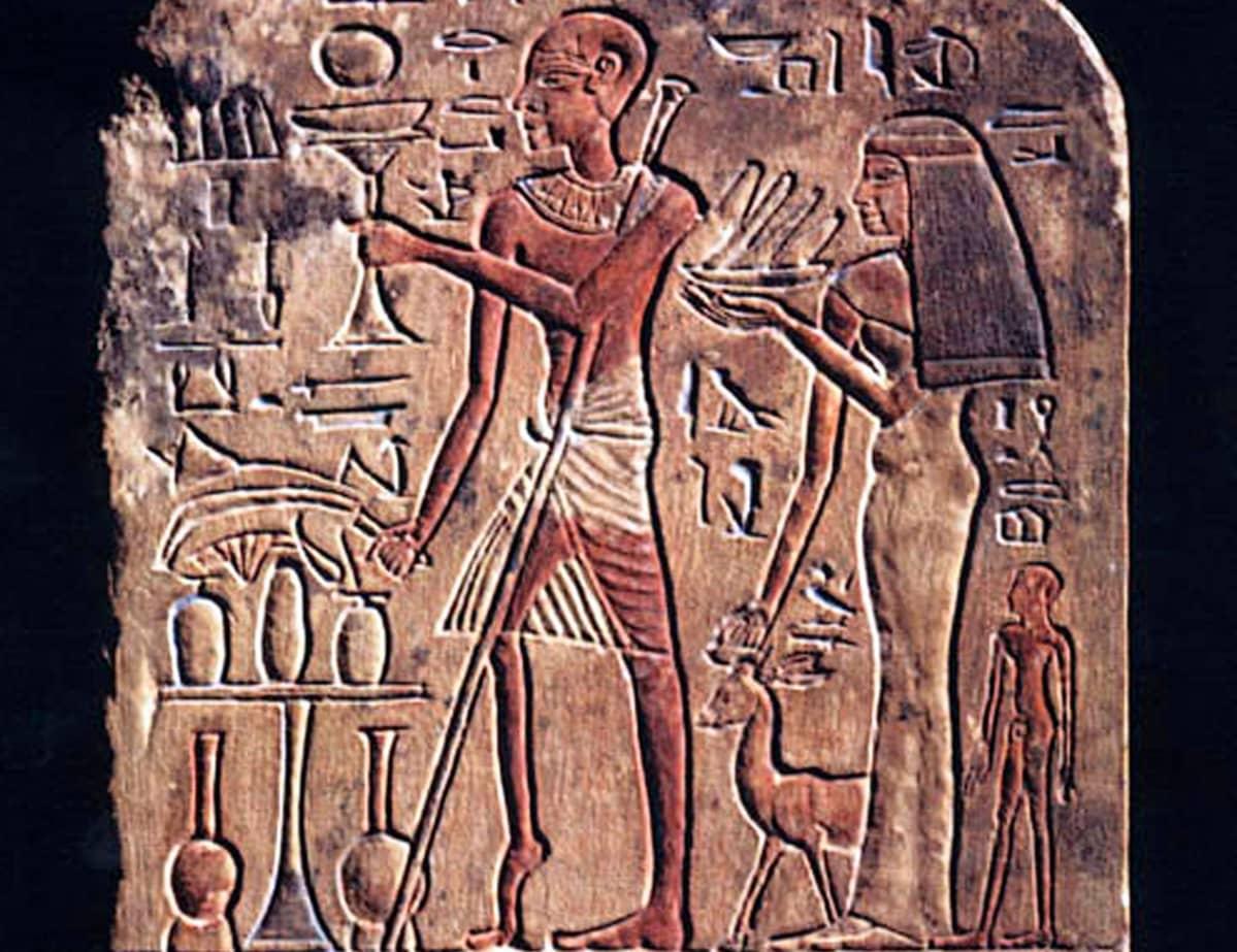 Egyotiläinen kivikaiverrus, jossa on lasia ja vatia pitelevät nainen ja mies. Miehen toinen jalka on kuihtunut, ja hänellä on sauva.