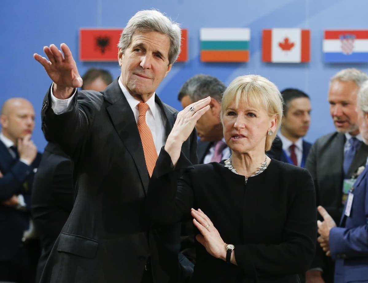 John Kerry ja Margot Wallström katsovat ohi kameran Kerryn käden osoittamaan suuntaan.