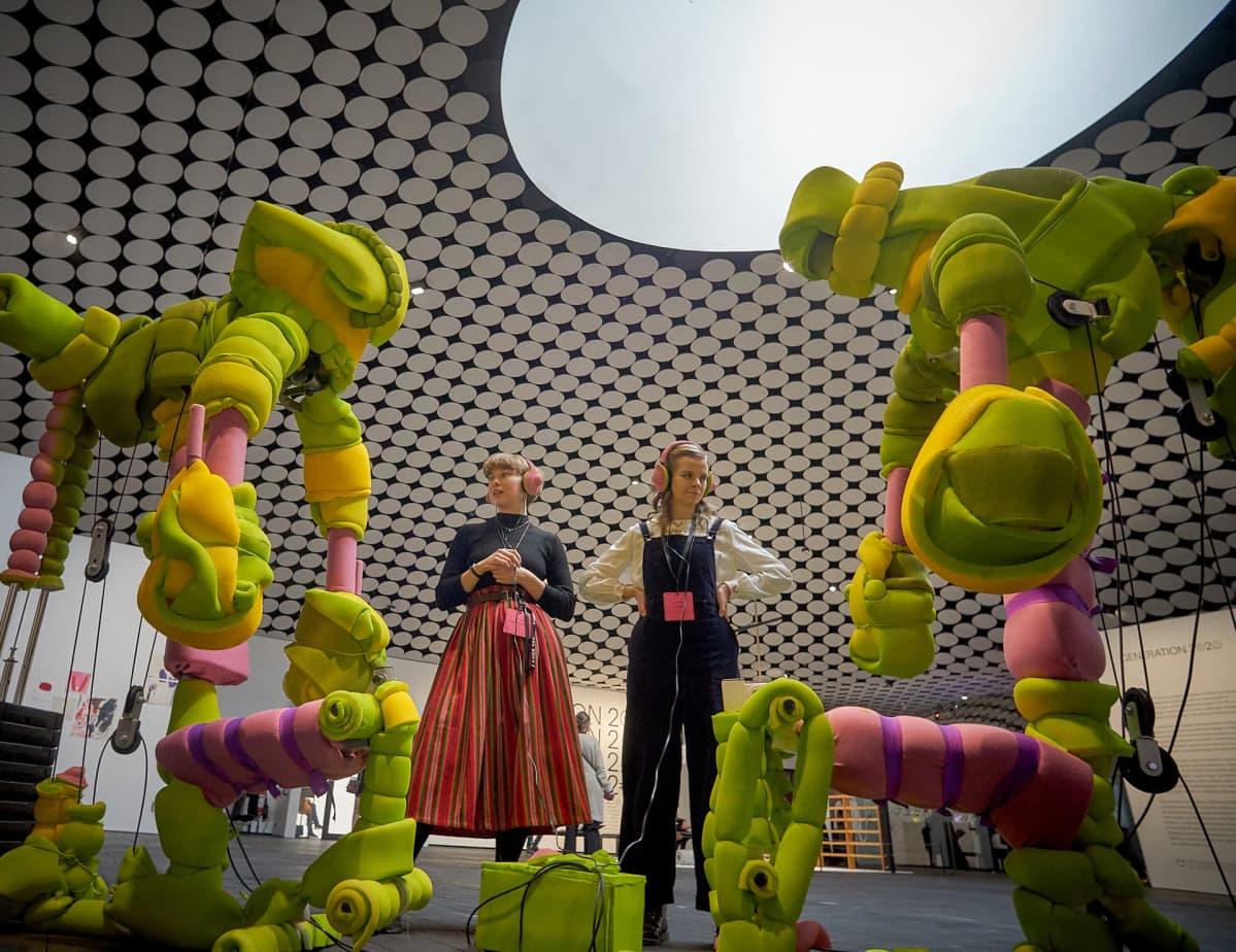 Kaksi naista kuulokeet päässä vihreän pehmoveistoksen ympäröimänä