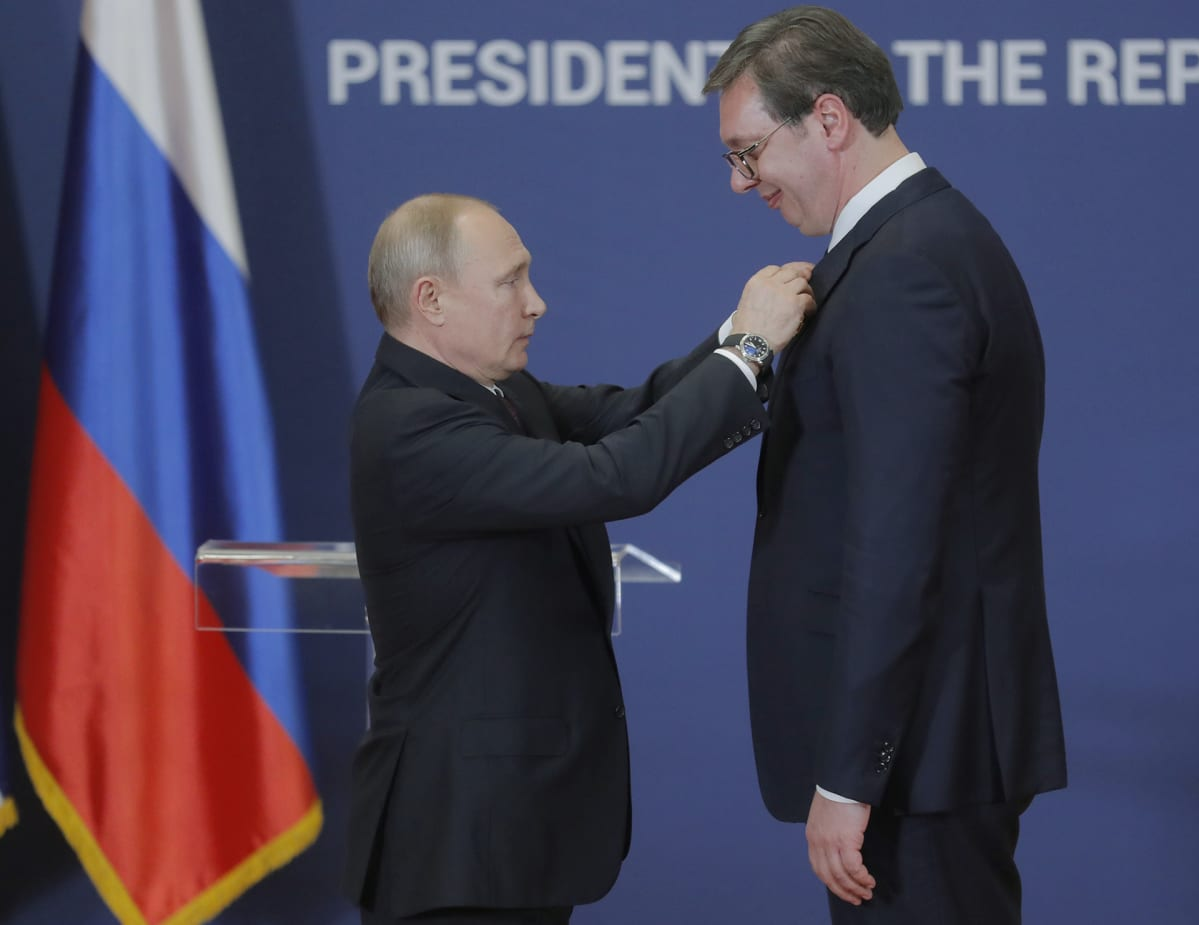Vladimir Putin kiinnittää kunniamerkin Alexandar Vucicin rintaan.