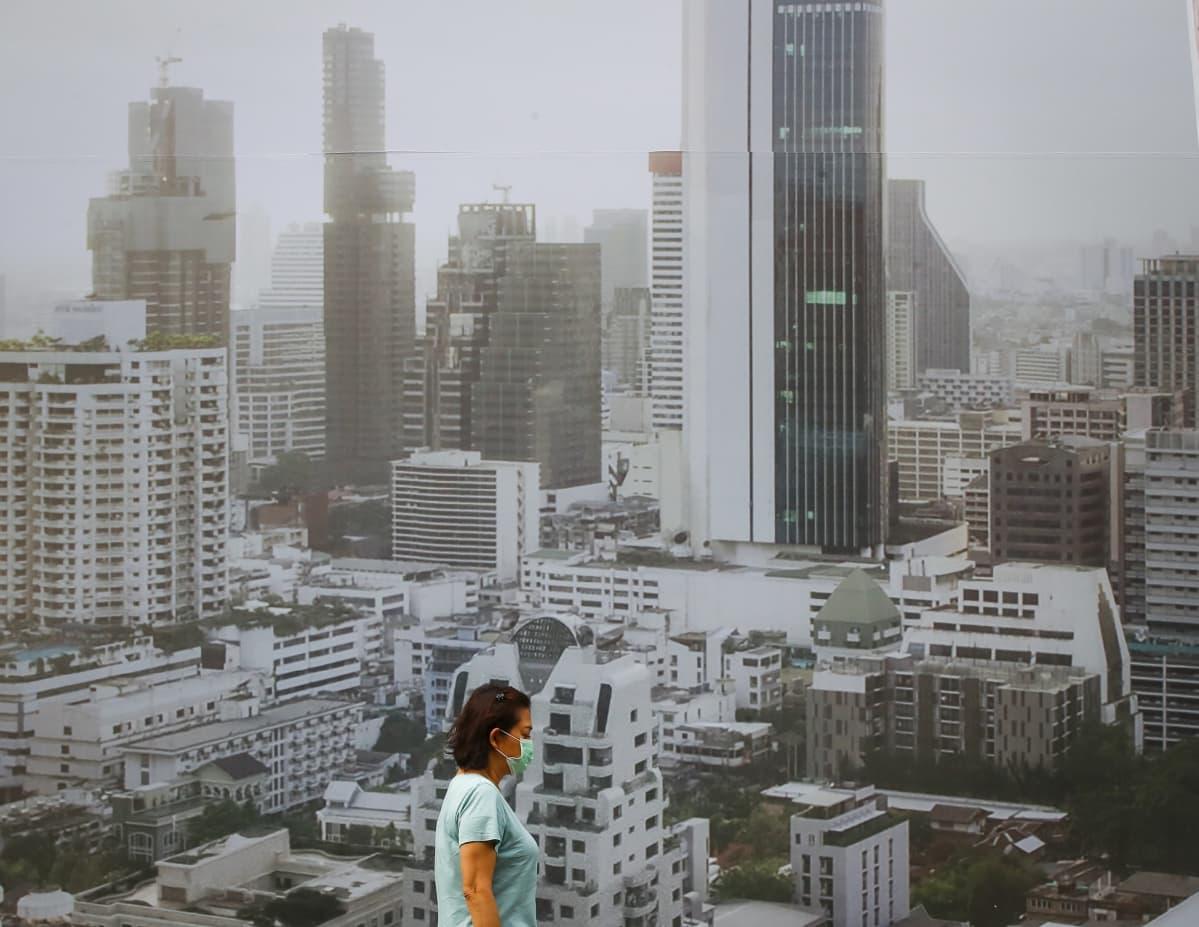 Nainen pitää hengityssuojainta Bangkokin saasteiden keskellä.