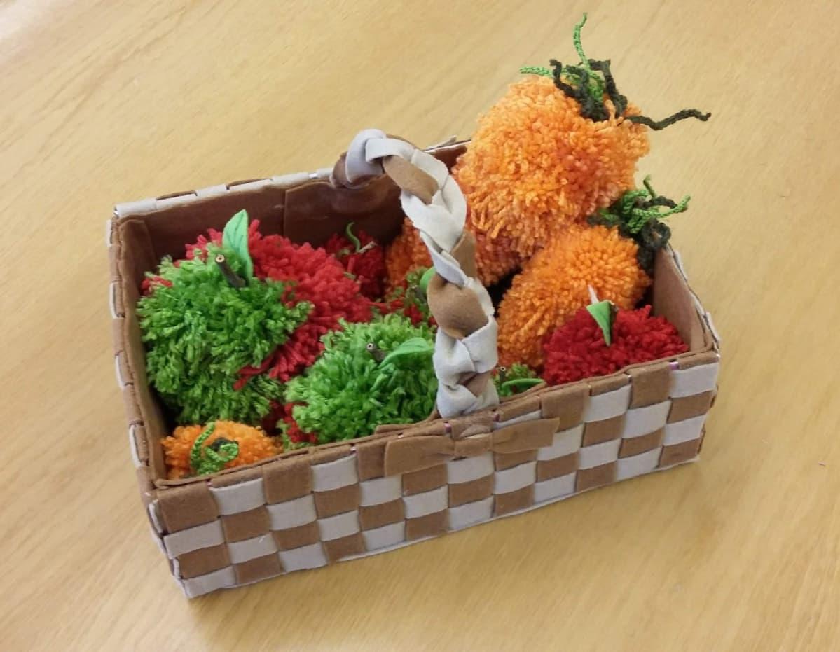 Lankatupsuista tehtyjä omenoita ja porkkanoita huopapunoksella päällystetyssä laatikossa.