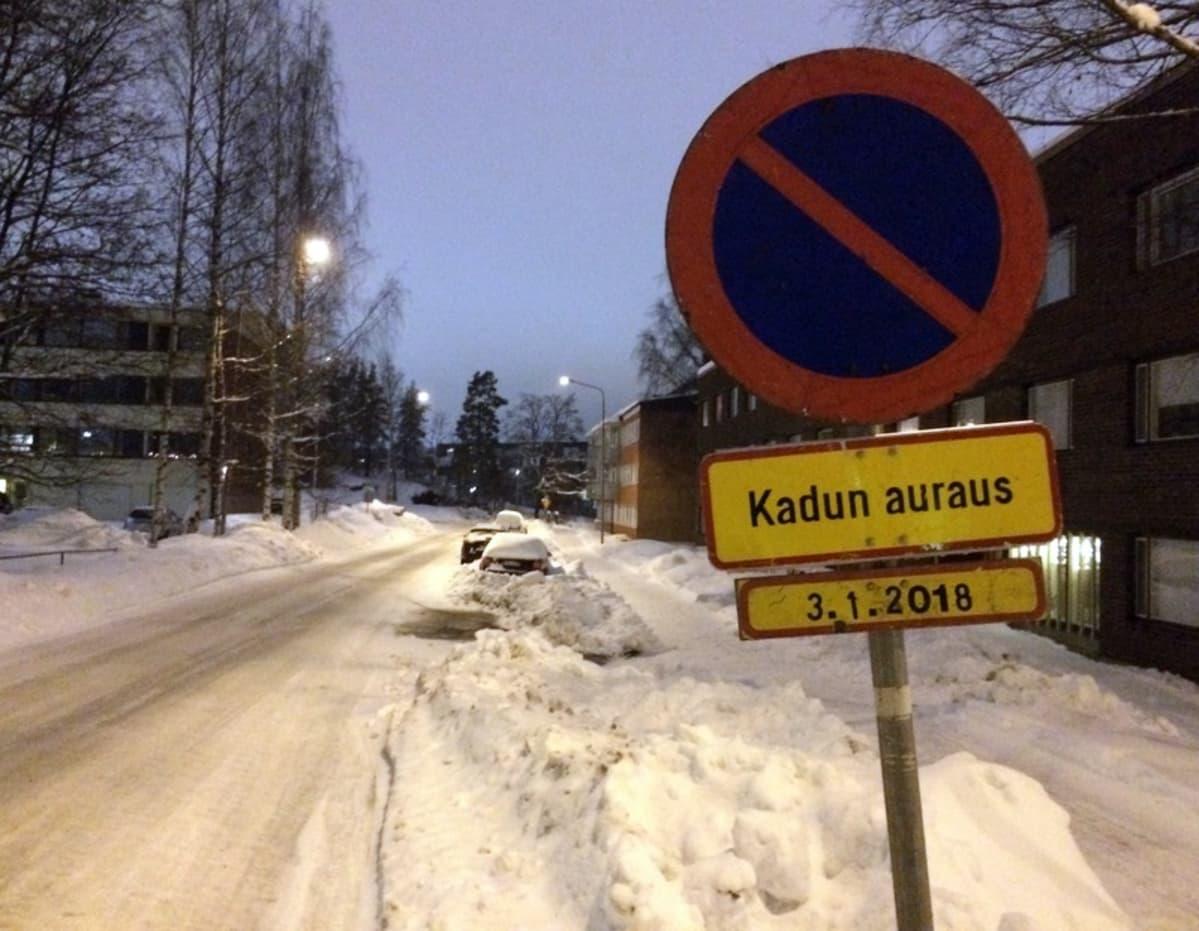 Väliaikainen pysäköintikieltomerkki lumisen kadun varressa