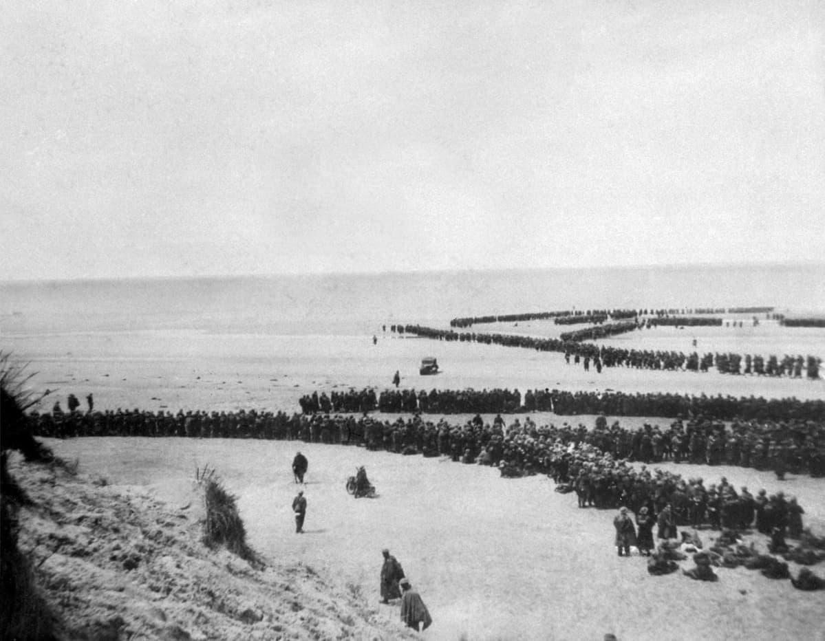 Suuri joukko sotilaita jonottaa rannikolla.