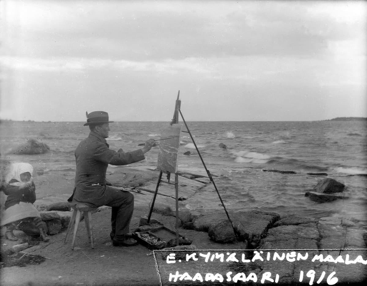 Mies maalaa taulua rannalla