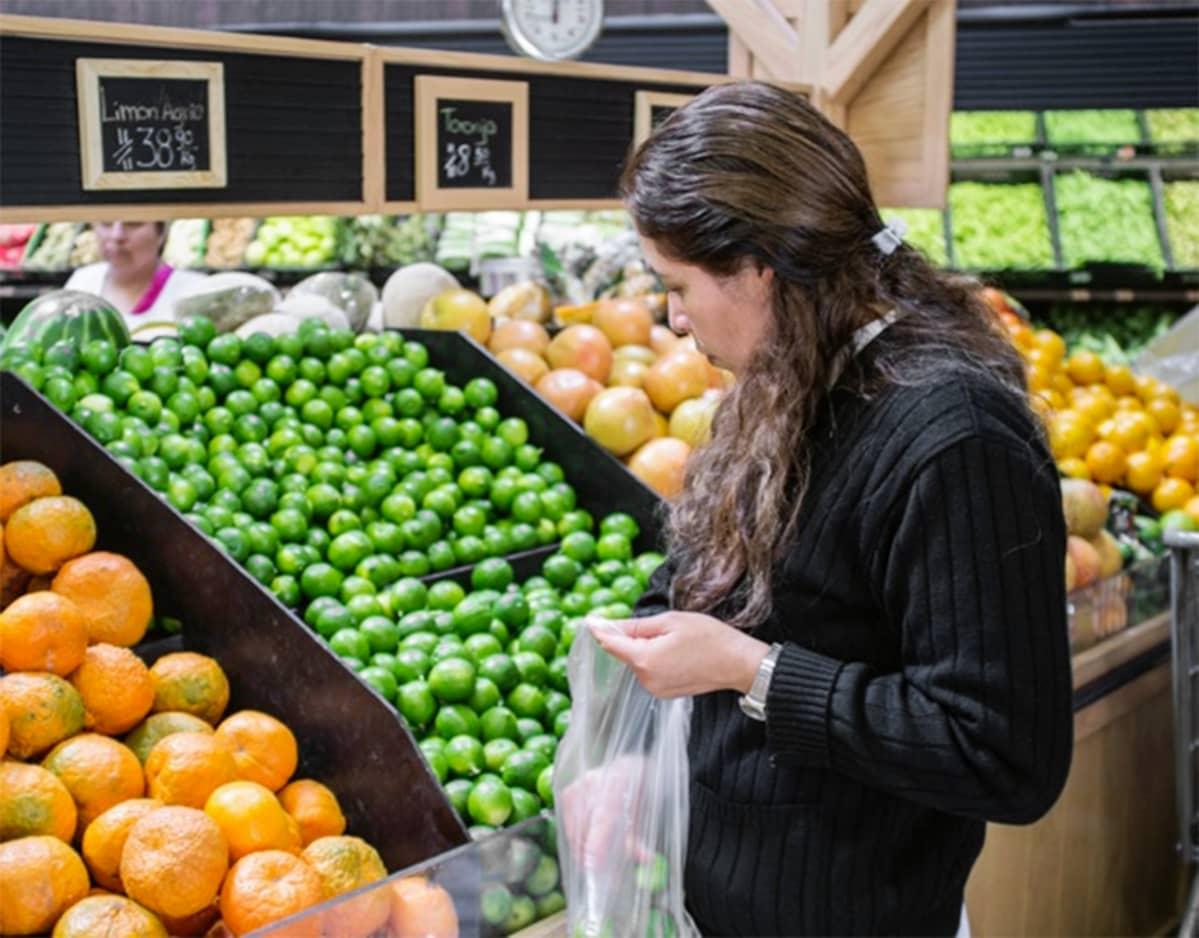 Nainen valitsee sitruksia hedelmätiskillä Meksikossa.