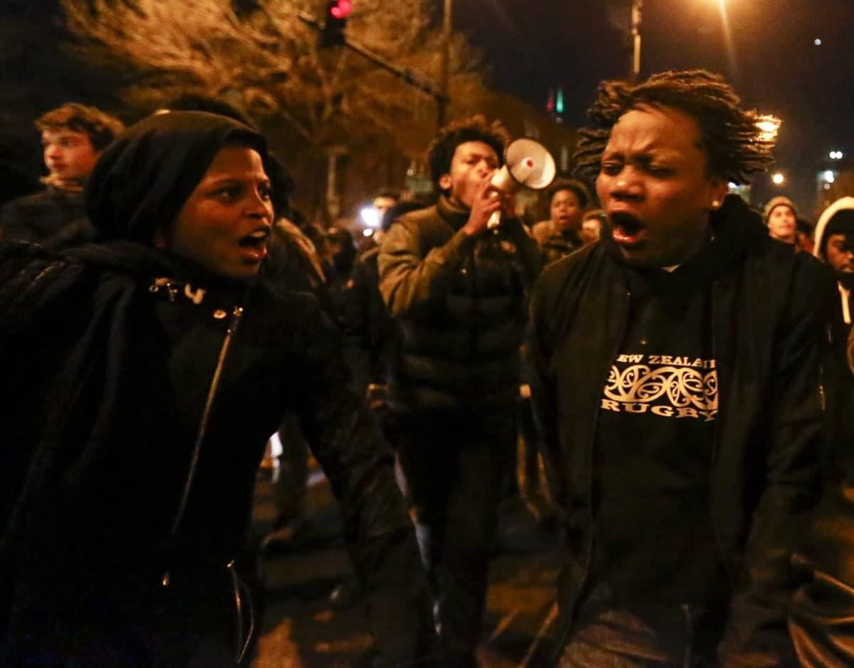 Nuoria mielenosoittajia huutamassa iskulauseita kadulla iltahämärässä.