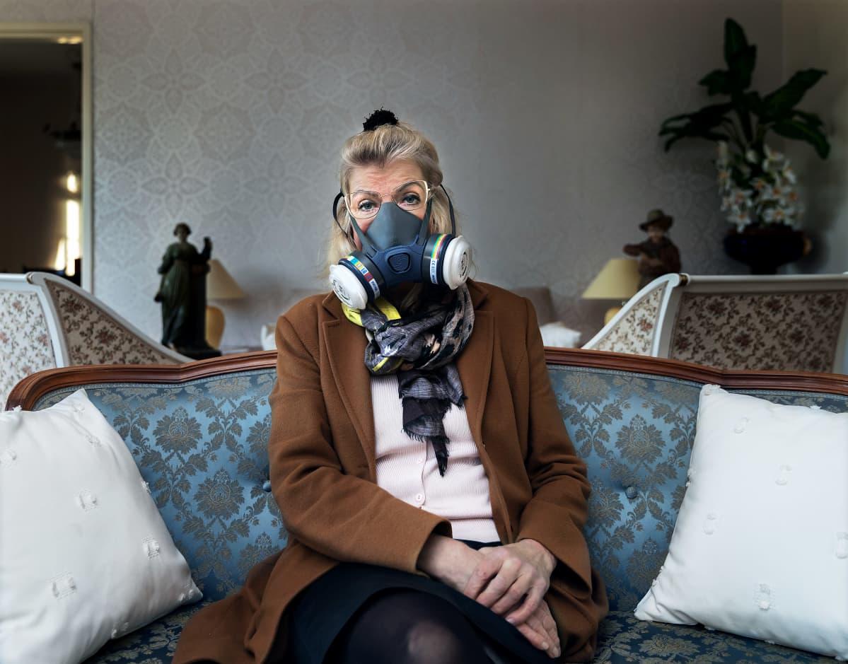 Terttu Aalto istuu sohvalla talonsa sisällä hengityssuojain kasvoillaan