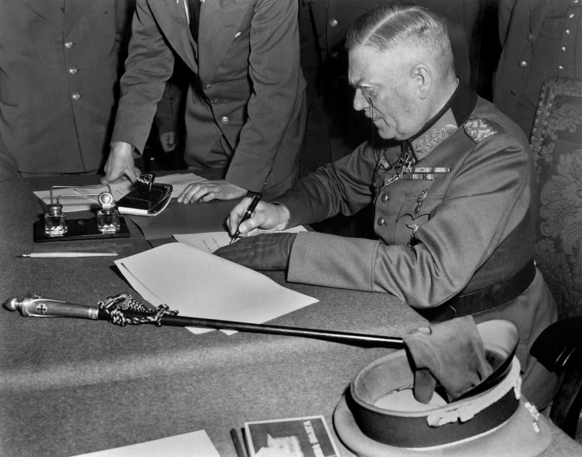 Univormupukuinen mies istuu pöydän ääressä kirjoittamassa