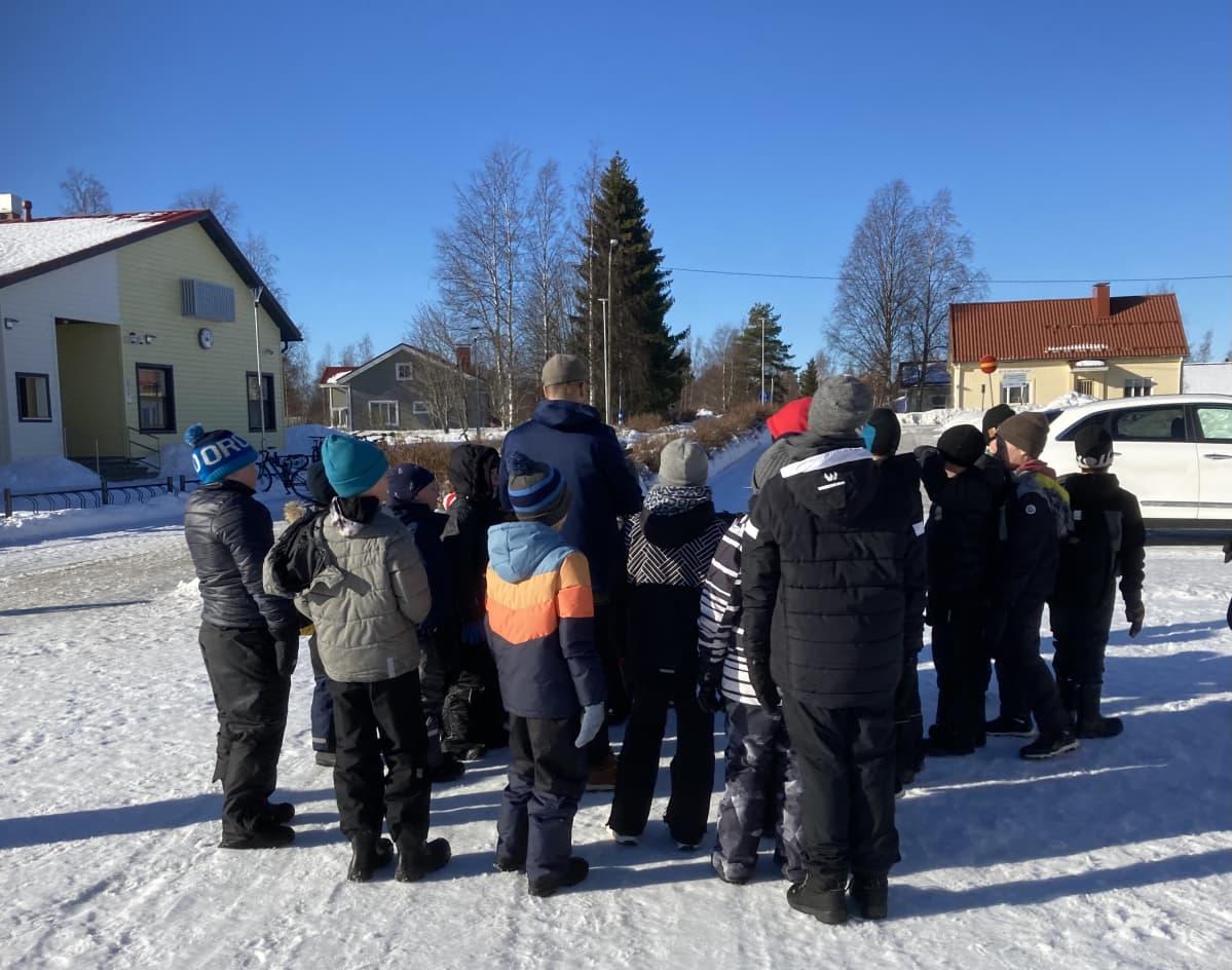 Joukko lapsia koulun pihalla Merijärvellä.
