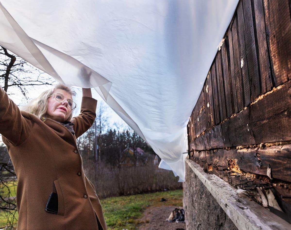 Terttu Aalto esittele talonsa ulkoseinää, jossa näkyy kreosoottia.