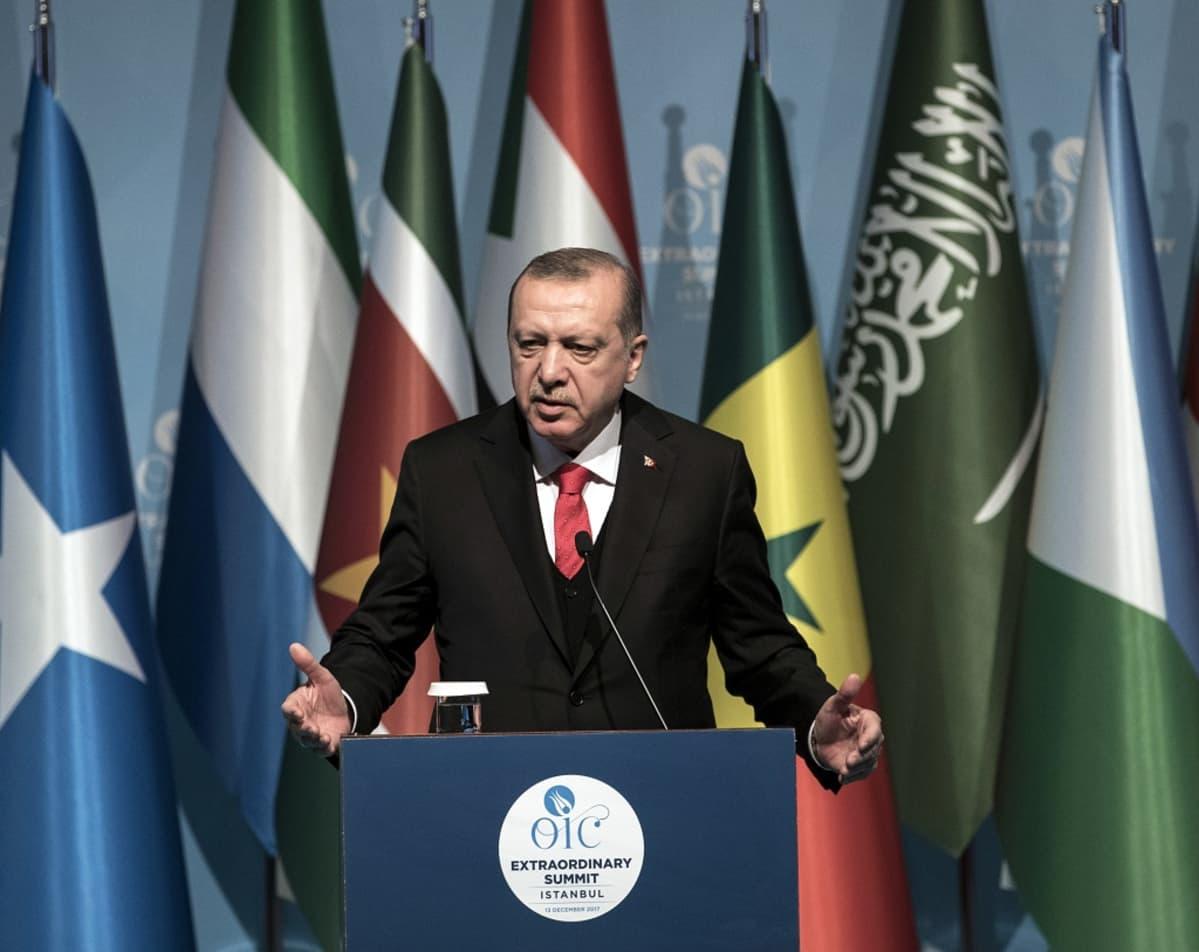 Erdoğan seisoo puhujankorokkeen takana ja puhuu mikrofoniin. Hänellä on tumma puku, liivit ja valkoinen kauluspaita sekä punainen kravatti. Taustalla on kokouksen Islamilaisen yhteistyöjärjestön jäsenmaiden lippuja.