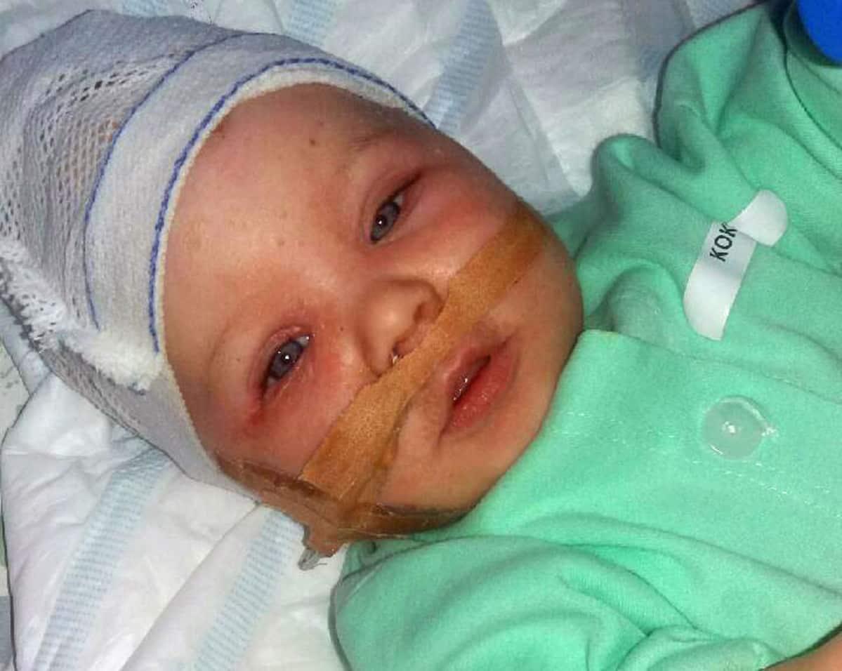 Vauva sairaalavaatteissa.