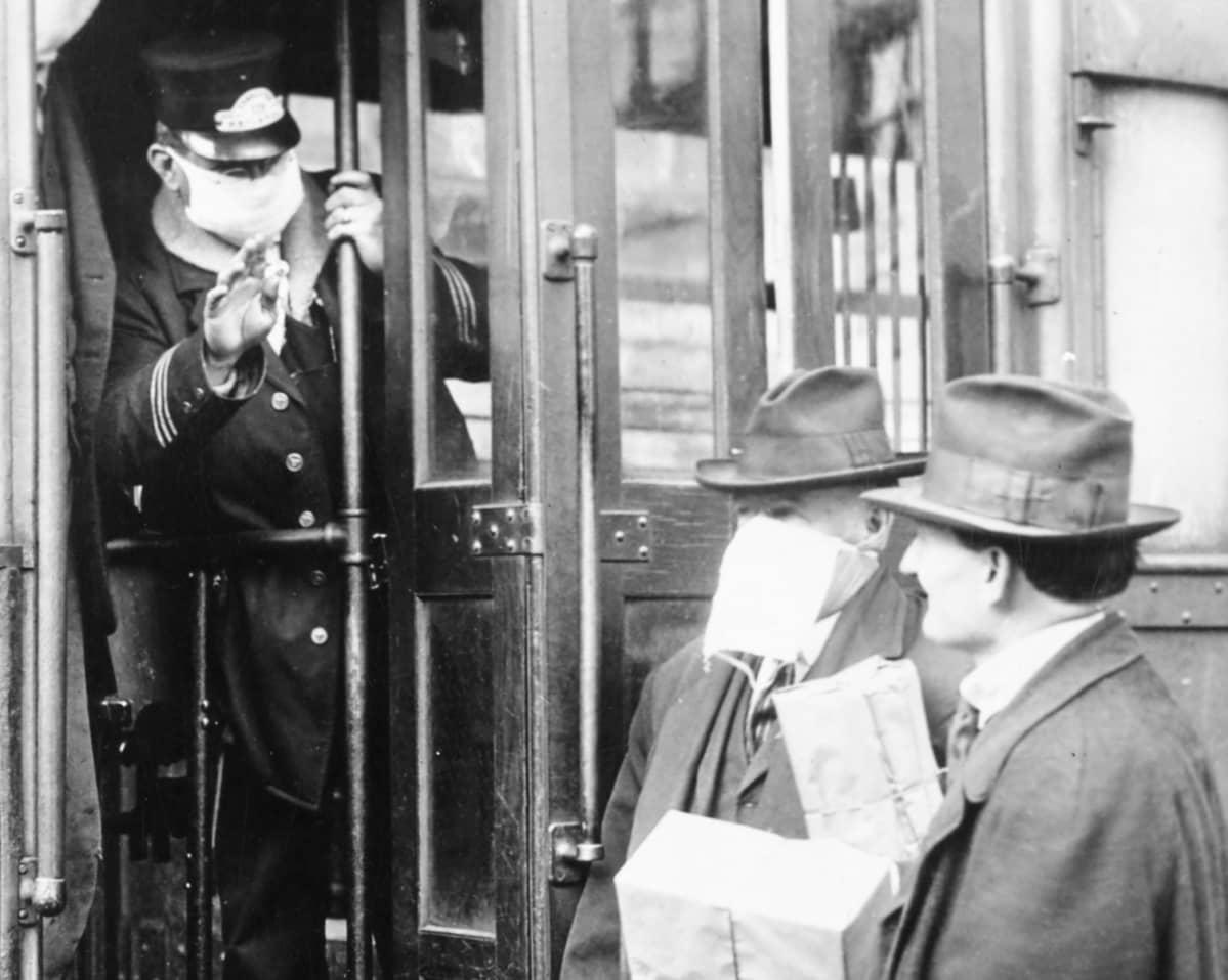 Raitiovaunun konduktööri estää ilman kasvosuojusta olevan matkustajan tulemisen vaunuun Seattlessa vuonna 1918.