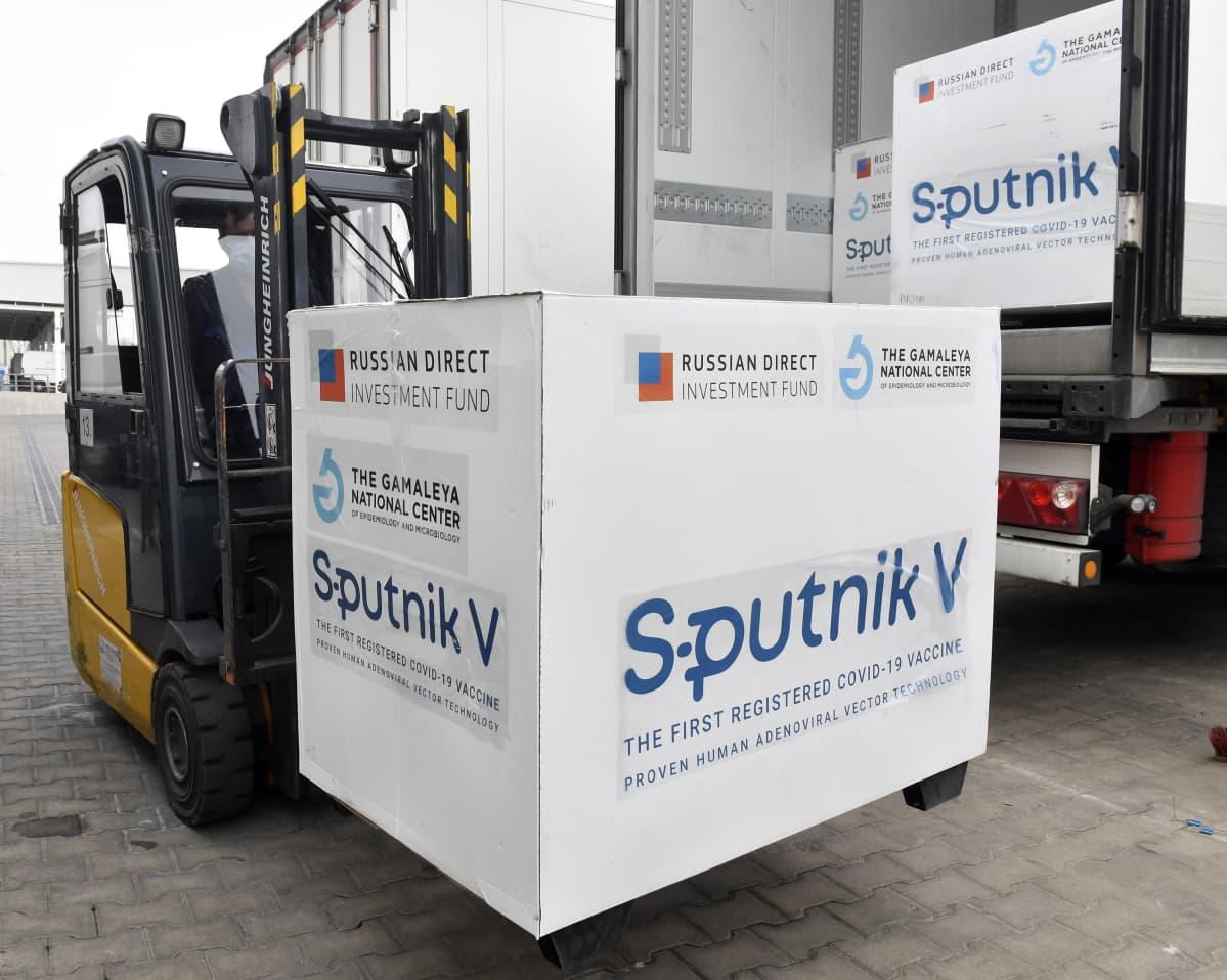 Trukki nostaa laatikkoa jonka kyljessä lukee Sputnik