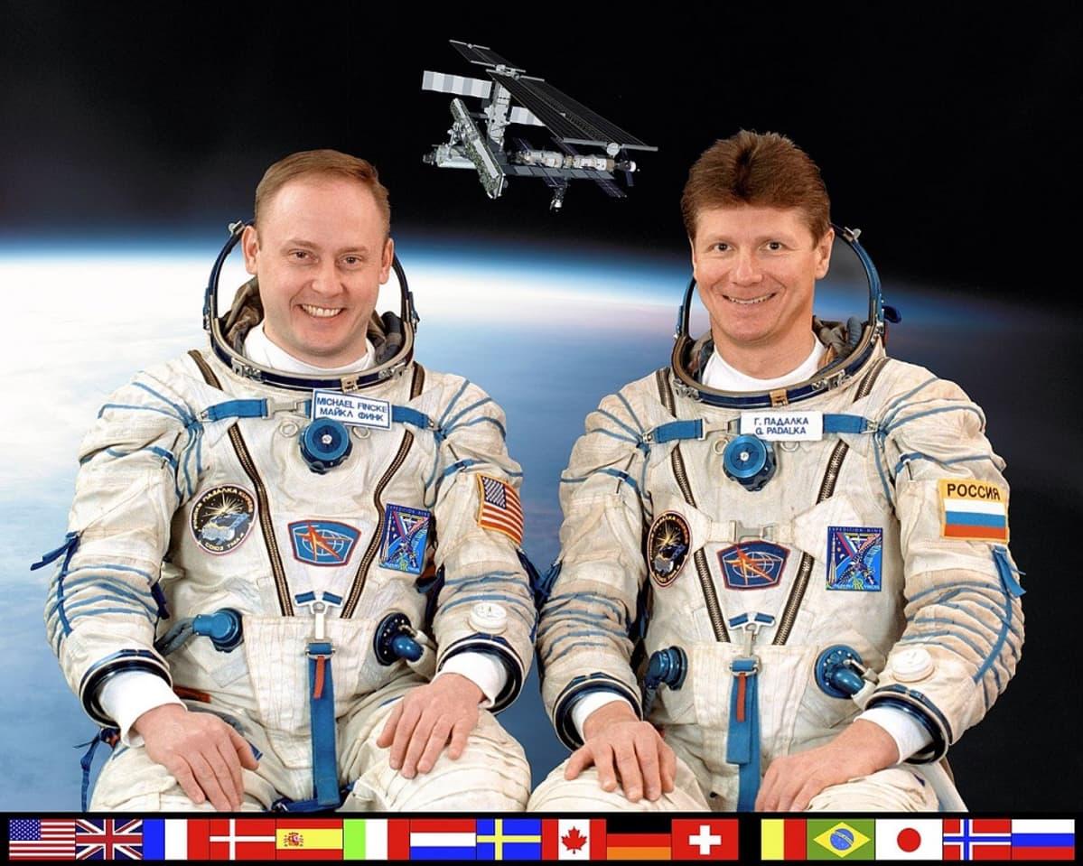 Kaksi avaruuspukuista miestä, taustalla kuva avaruusasemasta, alalaidassa 16 maan liput kertomassa, mistä maista ISS:llä on ollut väkeä.