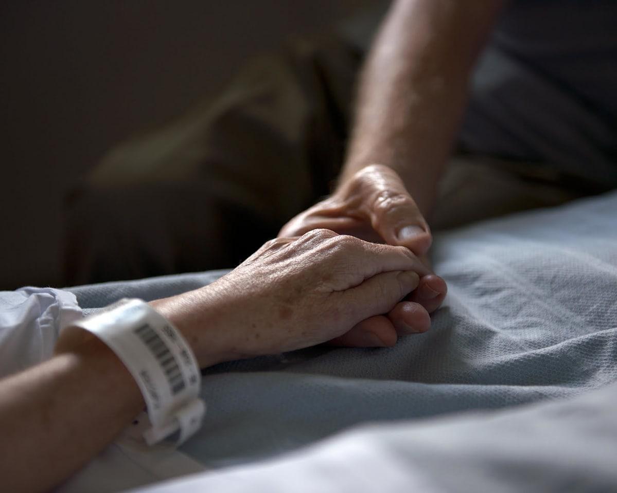 Valokuvateos, jossa kaksi ihmiset pitelevät toisiaan käsistä.
