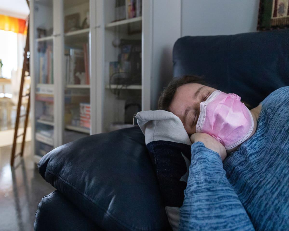 Sini Lindell lepää sohvalla kotonaan.