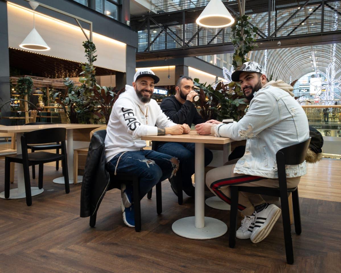 Itäkeskuksessa asuva James Jaba (vas) on kahvilla ostoskeskuksessa ystäviensä kanssa.