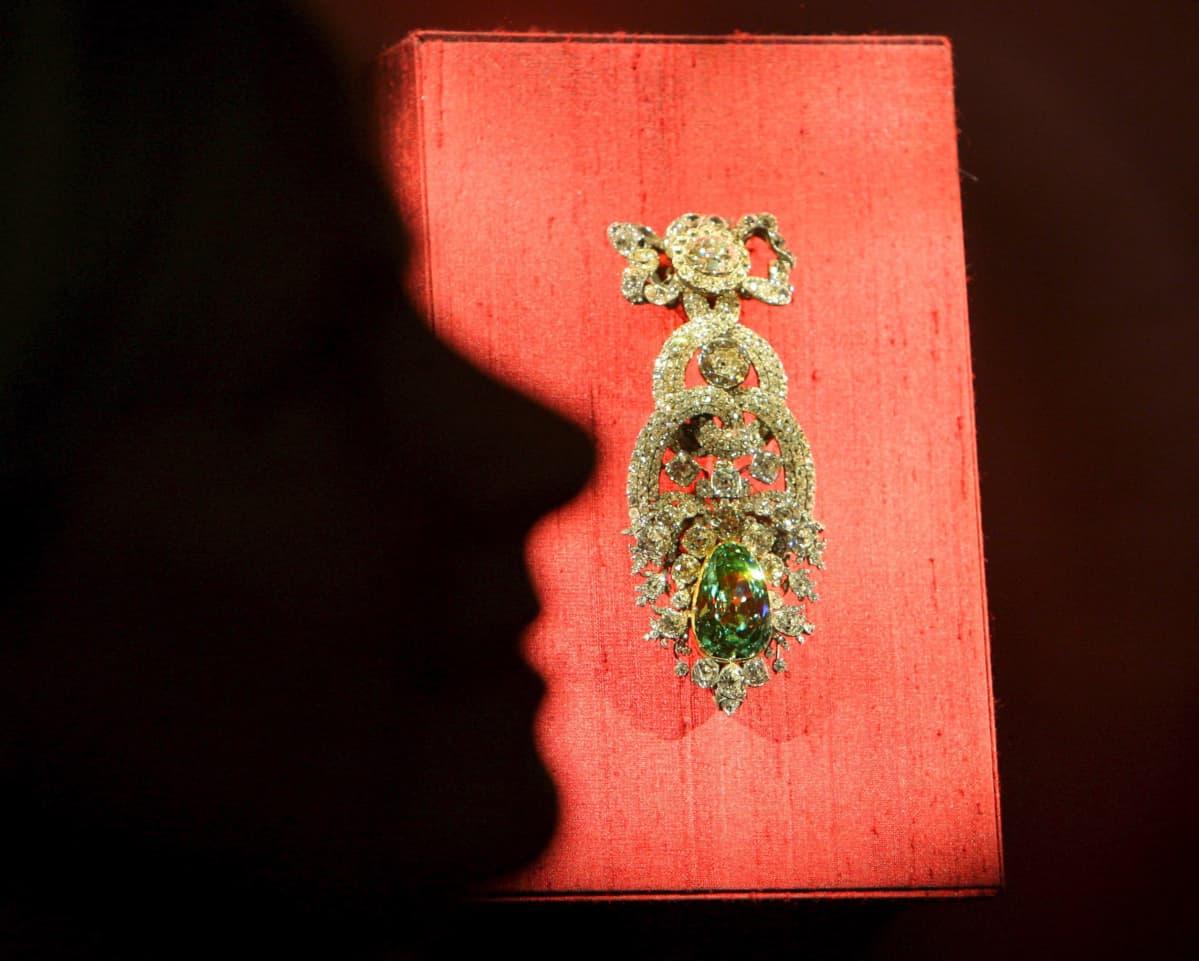 Työntekijän varjo heijastuu jalokivinäyttelyssä punaiselle silkkikankaalle asetetun Vihreä dresdeniläinen -timantin ylle.