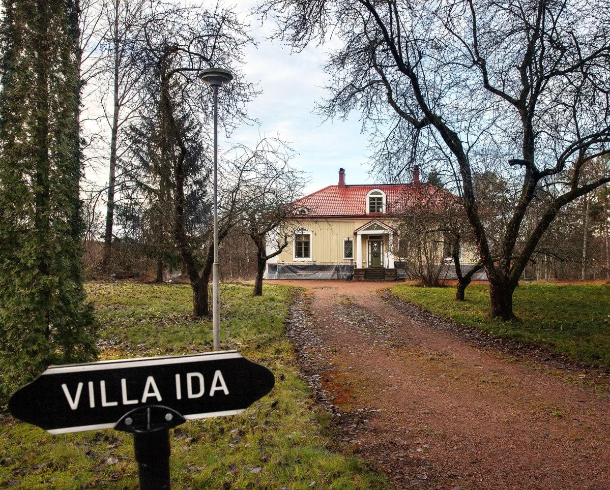Kyltti: Villa Ida ja taustalla talo