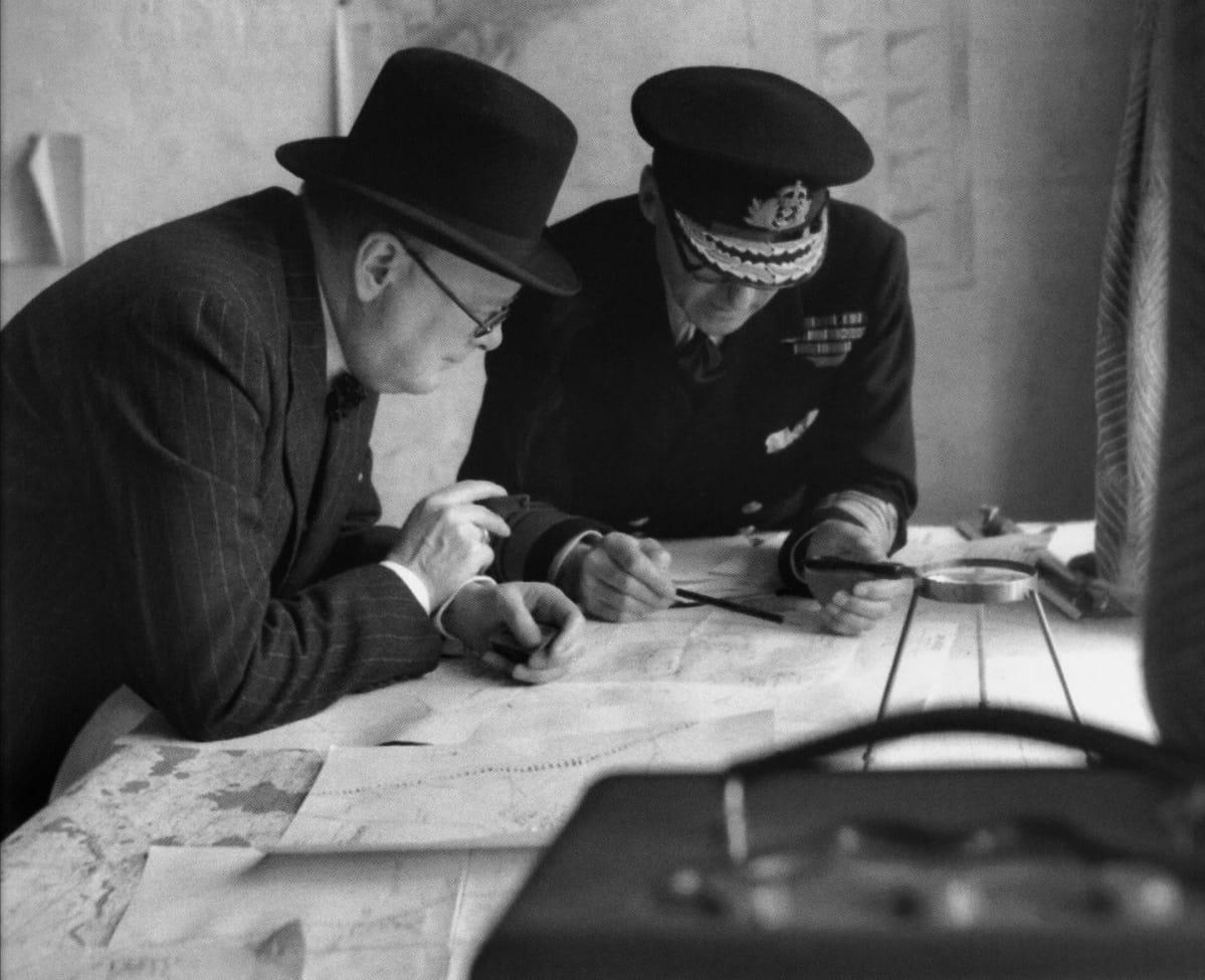 Pääministeri Winston Churchill ja amiraali Bertram Ramsey tutkivat karttaa.