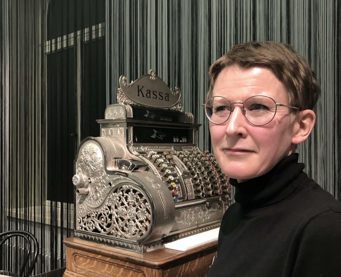Tutkija Katri Pyysalo vanhan kassakoneen edessä