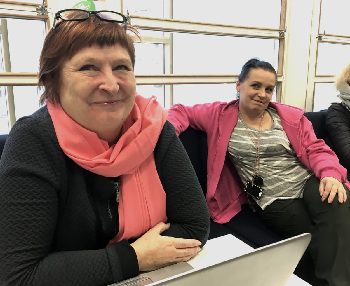 Projektipäällikkö Anne Haapalehto ja nuoriso-ohjaaja Piia Kallonen istuvat sohvalla koulun aulatilassa ja hymyilevät kuvaajalle.