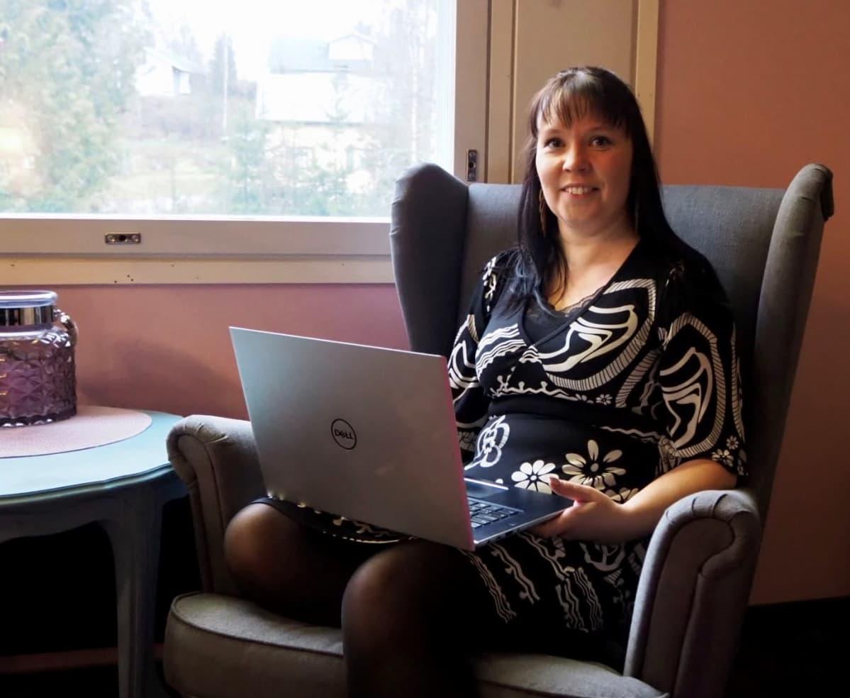 Seksuaaliterapeutti Susanna Syld istumassa nojatuolissa tietokone sylisään.