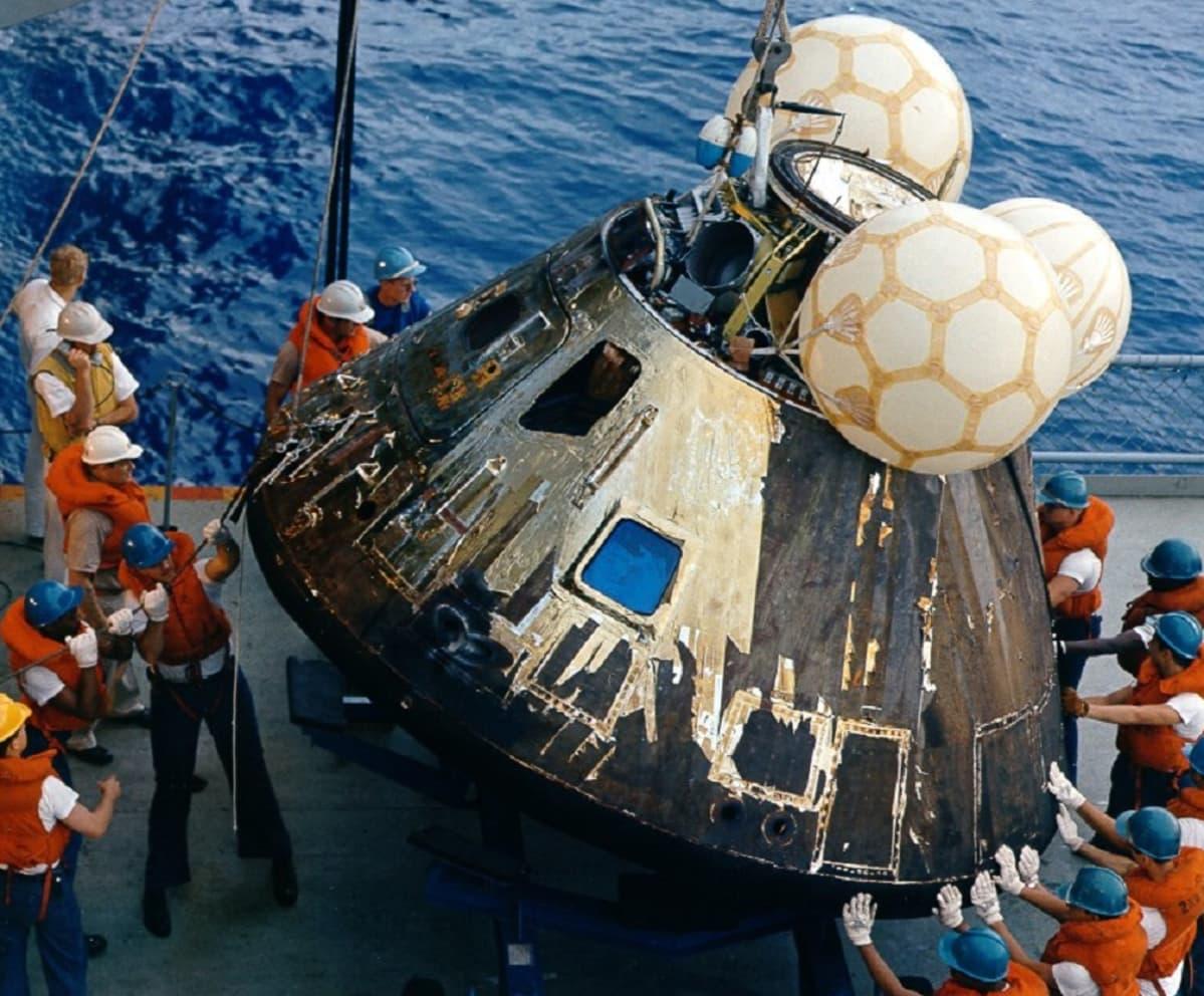 Pelastusliiveihin pukeutunut miesjoukko ohjailee kaapeleilla nostettavaa moduulia laivan kannelle. Moduulin päällä on kolme kelluketta.