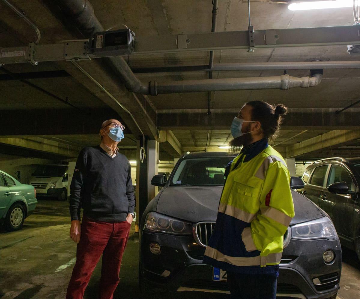 Timo Viljamaa, taloyhtiön puheenjohtaja ja Tatu Vattulainen, työnjohtaja, katsovat sähkönjohtoja vievää palkkia parkkihallin katossa.