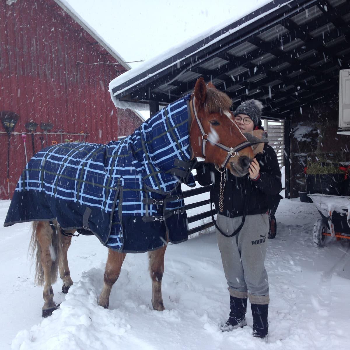 Janina Tiihonen hevosen kanssa lumisateessa