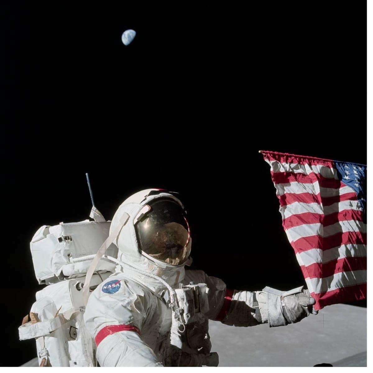Astronautti pitelee kiinni lipun kulmasta. Taustalla avaruudessa häämöttää maapallo.