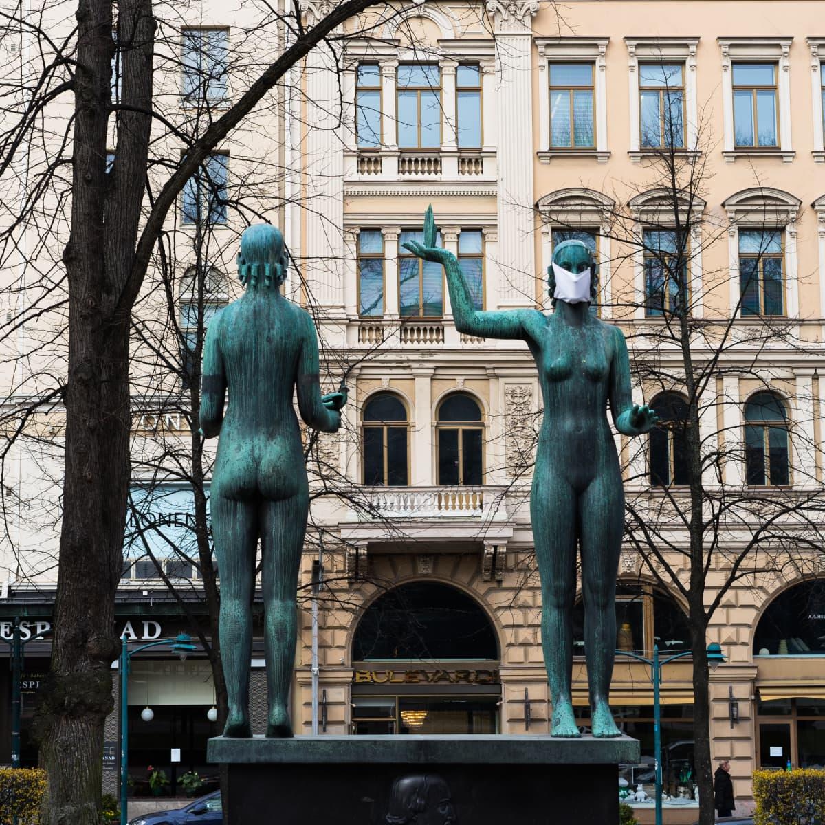 Taru ja Totuus -veistos Herlsingin Esplanadin puistossa. Vuonna 1932 paljastettu teos on omistettu Zachris Topeliuksen muistolle. 31.3.2020 se oli saanut koronavirusajan hengessä hengityssuojan.