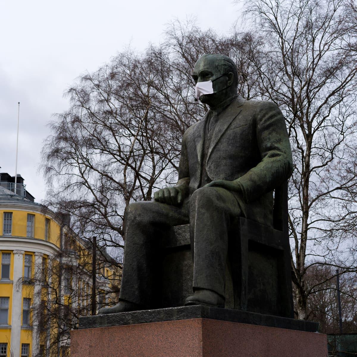 Kyösti Kallion patsas eduskuntatalon edessä hengityssuojan kanssa 31.3.2020.