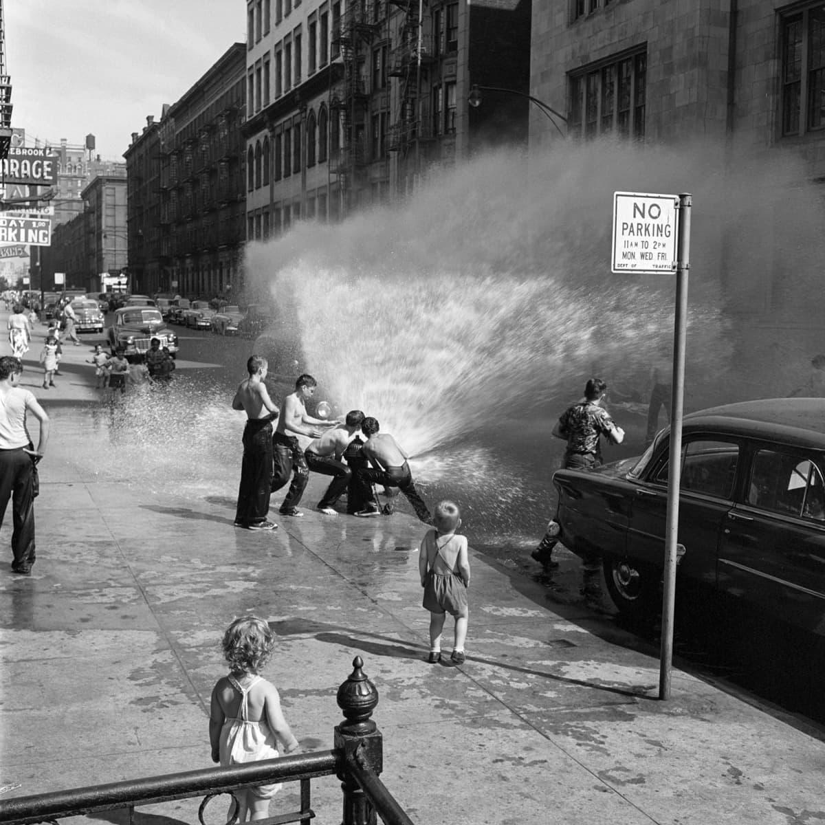 Lapset suihkuttavat vettä palopostista kadulla.