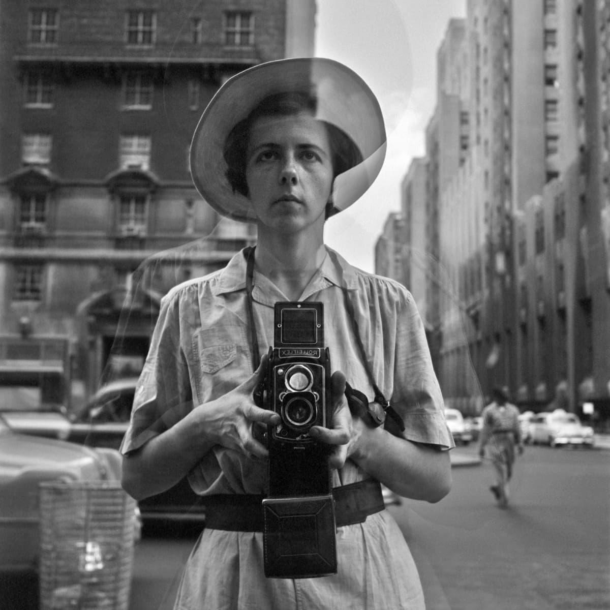 Vivian Meyerin omakuva näyteikkunan heijastuksessa.