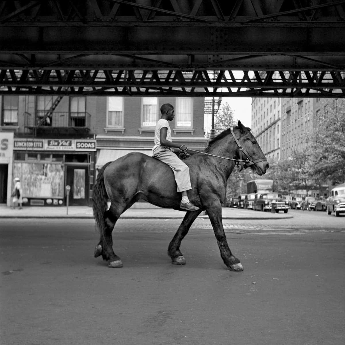 Mies ratsastaa kadulla sillan alla.