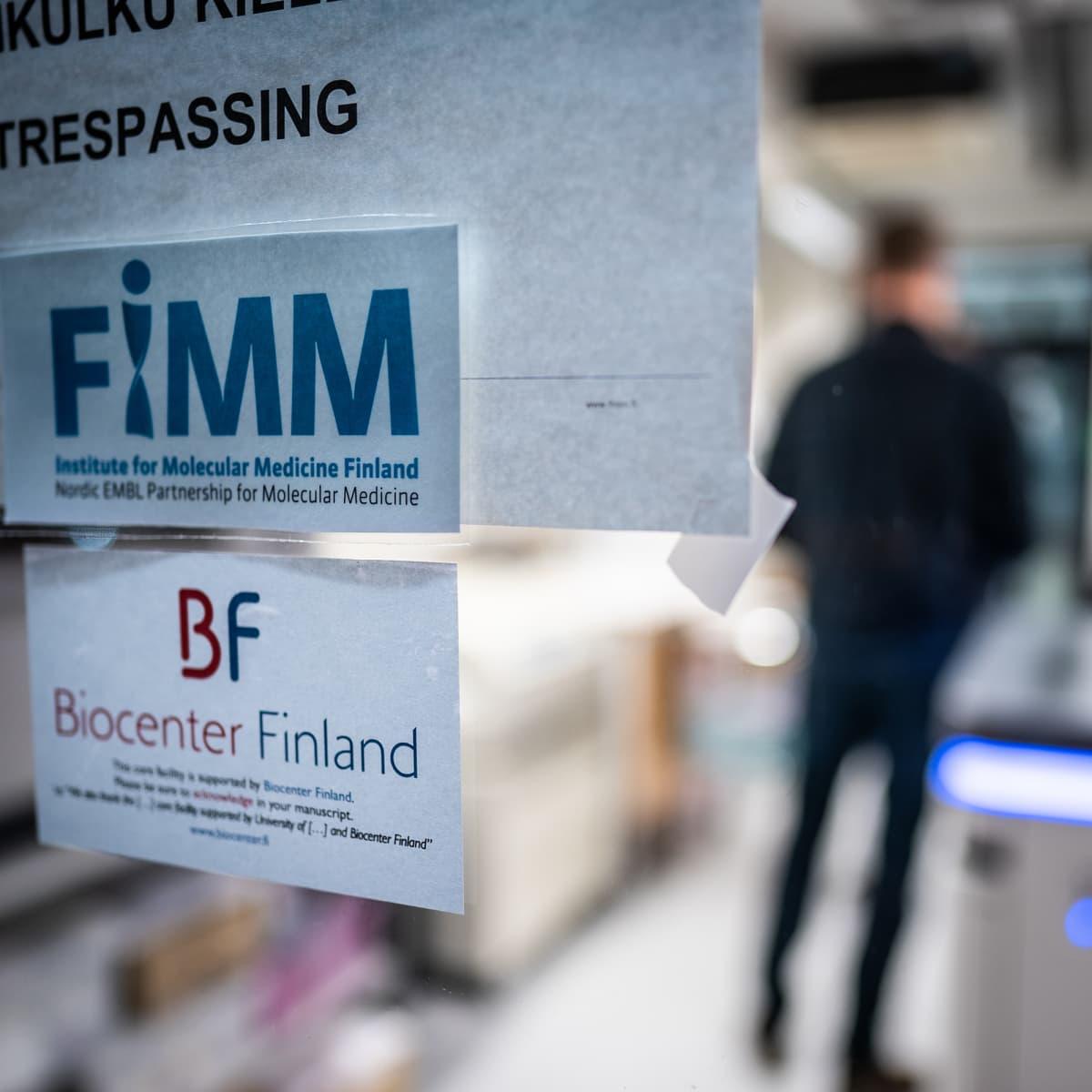 FIMM-teksti paperilapussa laboratorion lasiovessa, oven läpi näkyy mieshahmo.