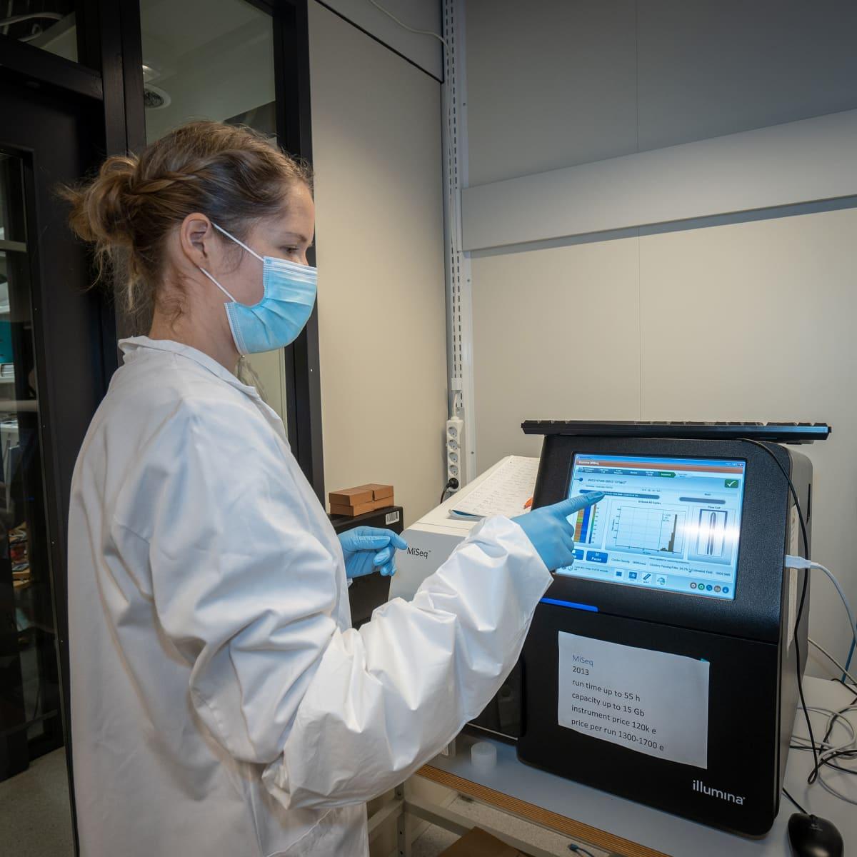 Tutkija Sari Hannula tutkii sekvensaattorin näyttöä FIMMin laboratoriossa.