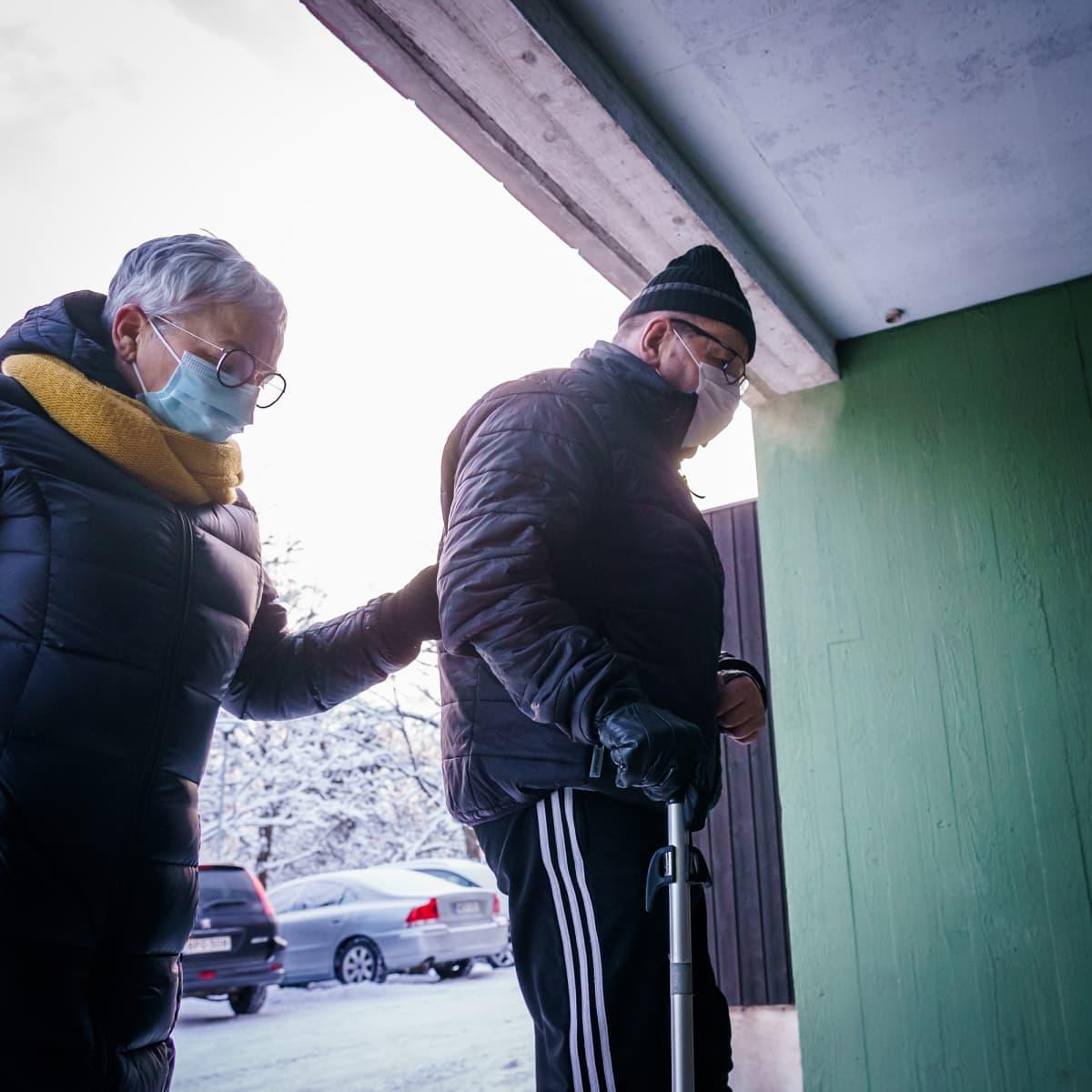 Omaishoitaja Marja-Liisa Saarinen tukee kepin kanssa kulkevaa miestään Reijoa matkalla taksista kotiovelle.