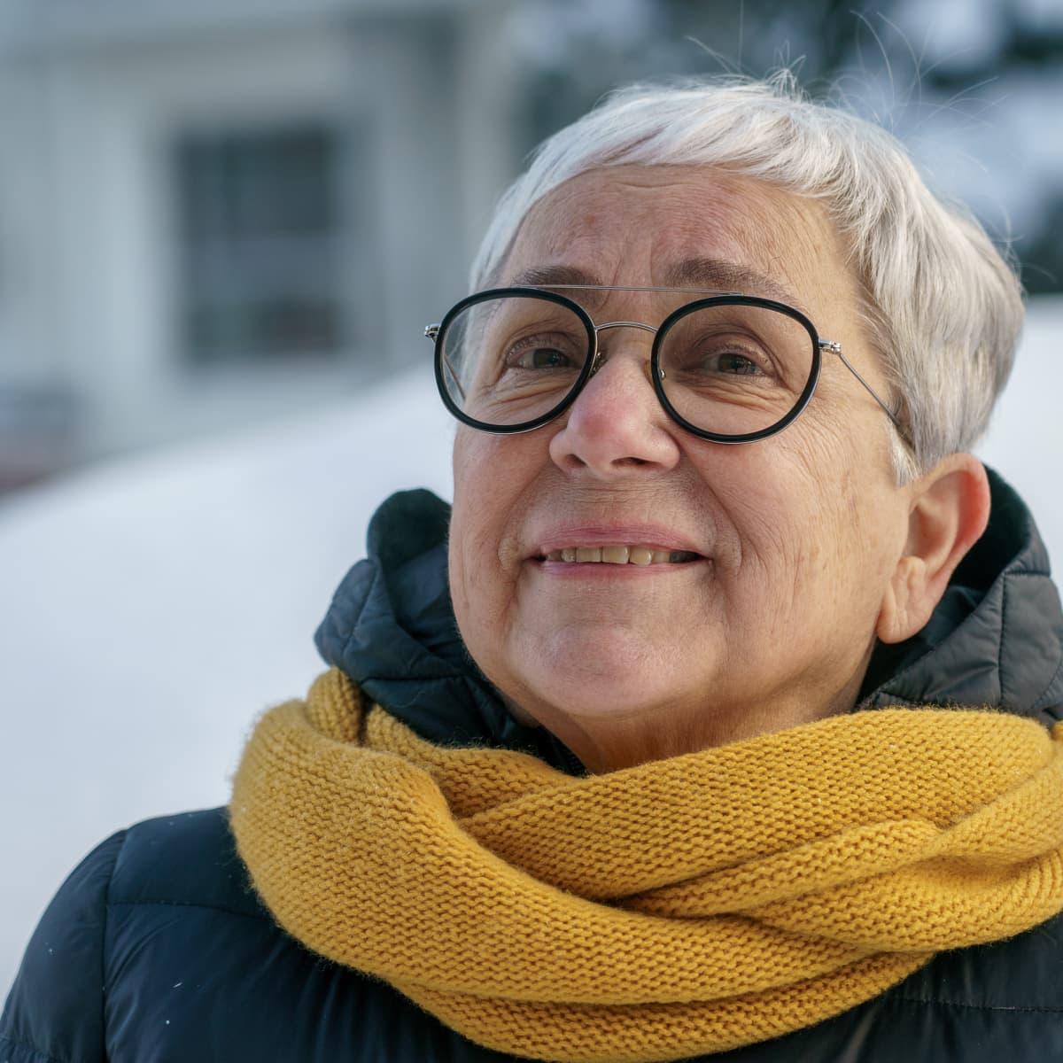 Omaishoitaja Marja-Liisa Saarinen ulkovaatteissa henkilökuvassa.