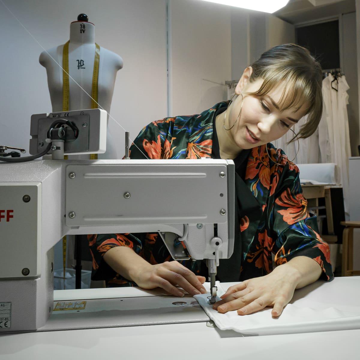 Hääpukusuunnittelija Laura Hyvi ompelemassa ompelukoneella.
