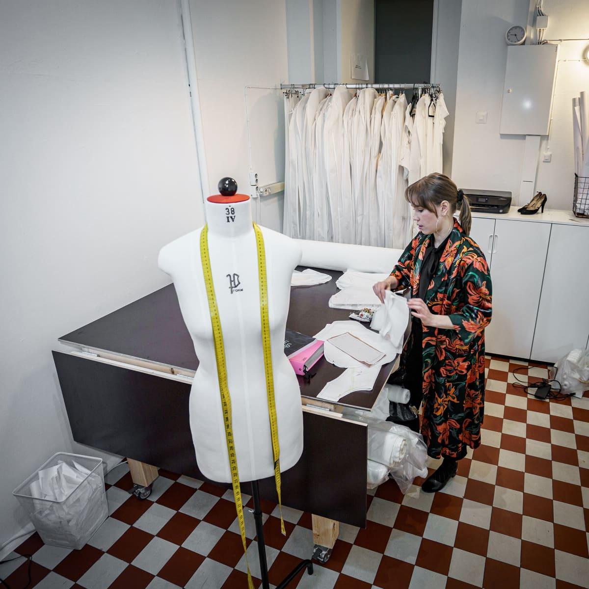 Hääpukusuunnittelija Laura Hyvi työskentelemässä työpöytänsä ääressä.
