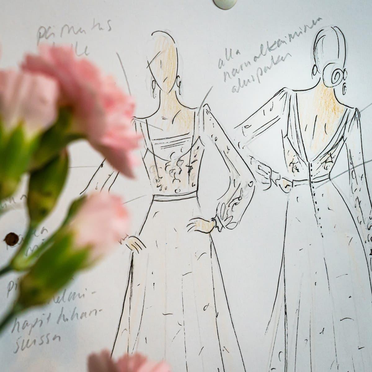 Hääpukusuunnittelija Lara Hyvin luonnospiirustuksia, etualalla vaaleanpunaisia kukkia.