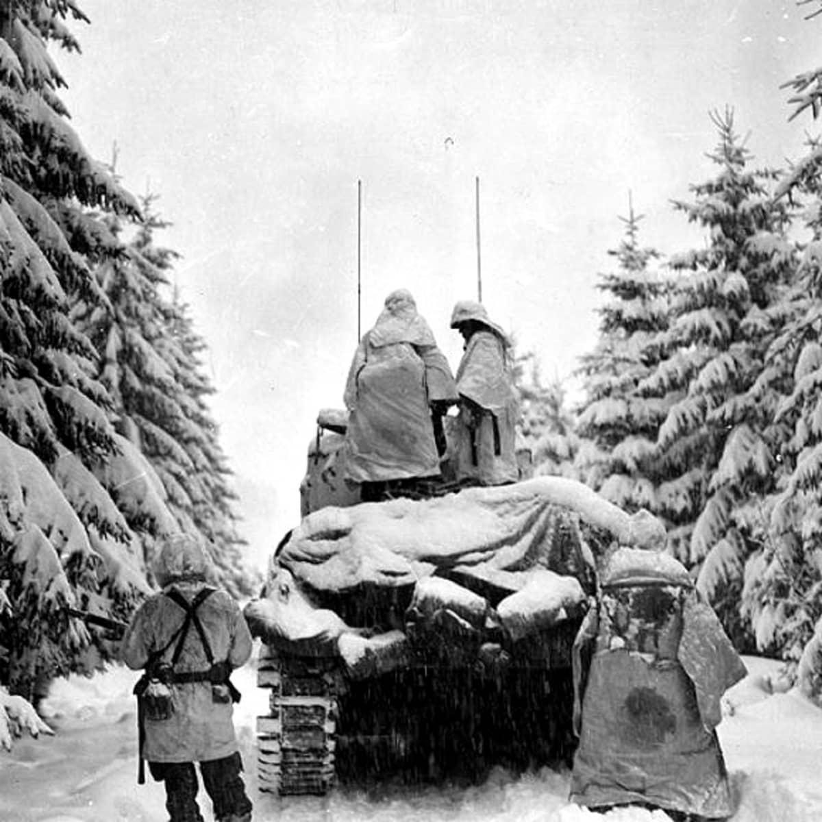Yhdysvaltain armeijan panssarivaunu ja sotilaita etenemässä Ardennien taistelun aikana.