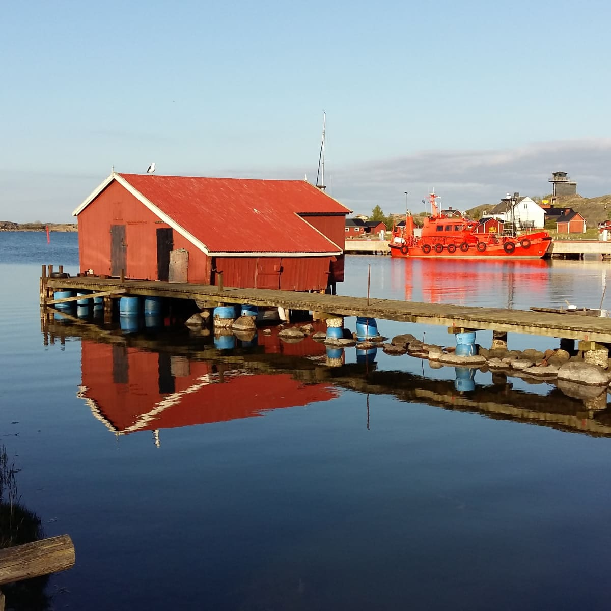 Hamnen i Utö med båthus och en lotskutter som speglas i vattnet.